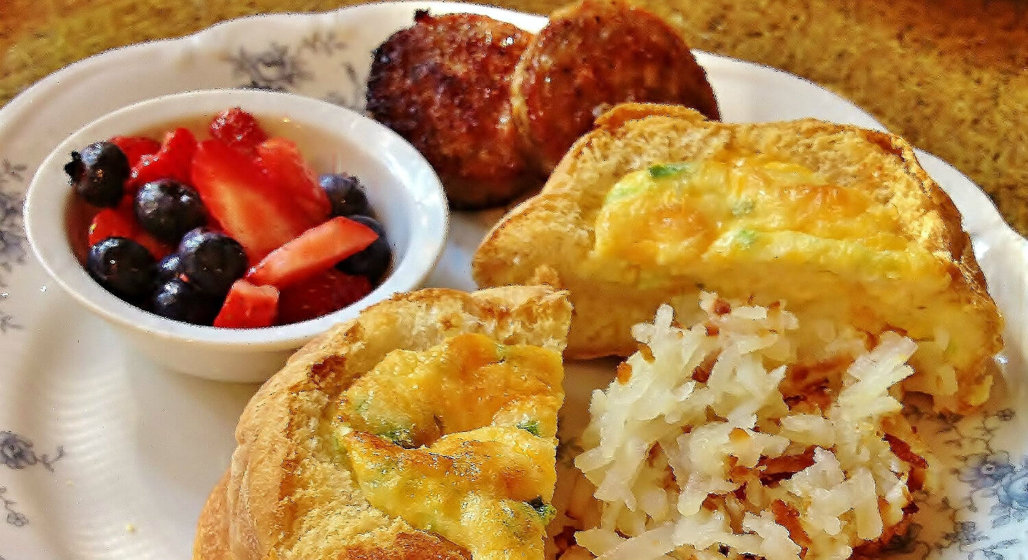 Lavish breakfast dish includes golden hash browns, egg dish, colorful fruit, and a muffin