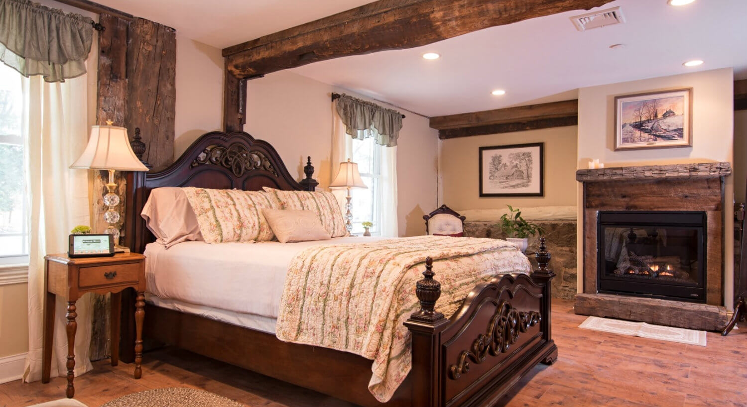 Cozy bedroom with natural wood fireplace and trim; featuring dark wood bed with white linens
