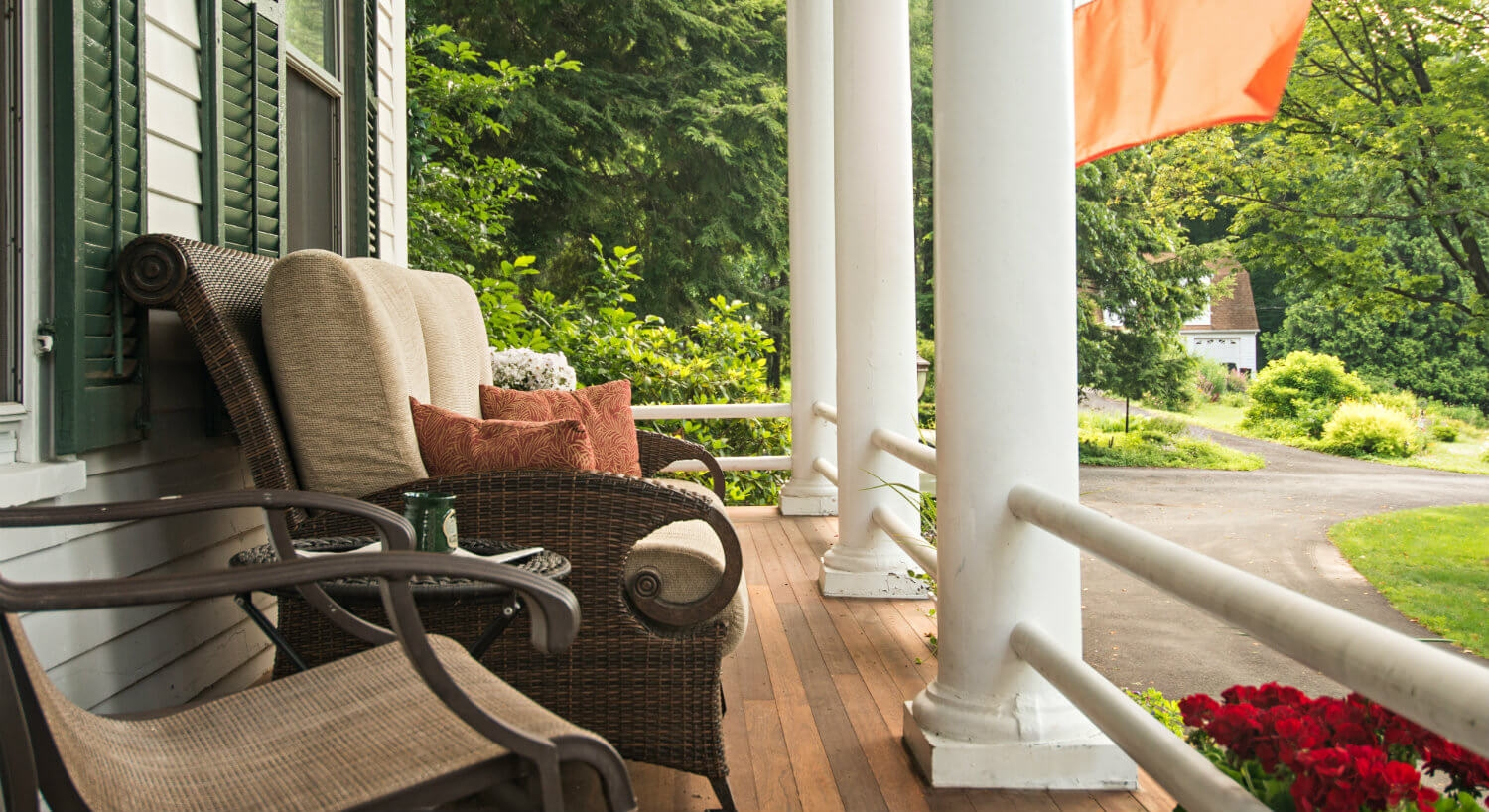 Cozy front porch setting with large white columns and comfortable seating for numerous people