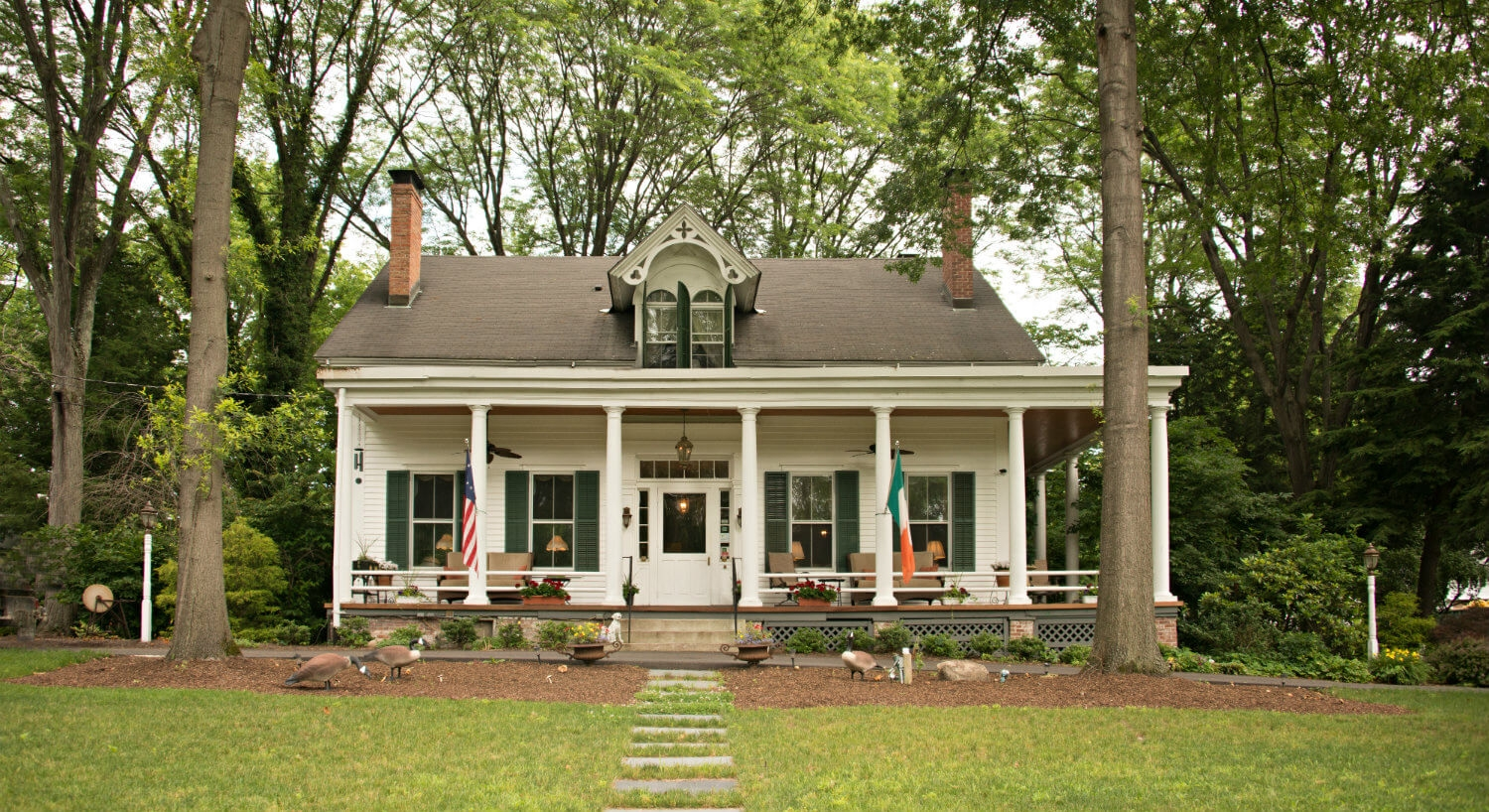 White cottage nestled among tall green trees; features cozy front porch