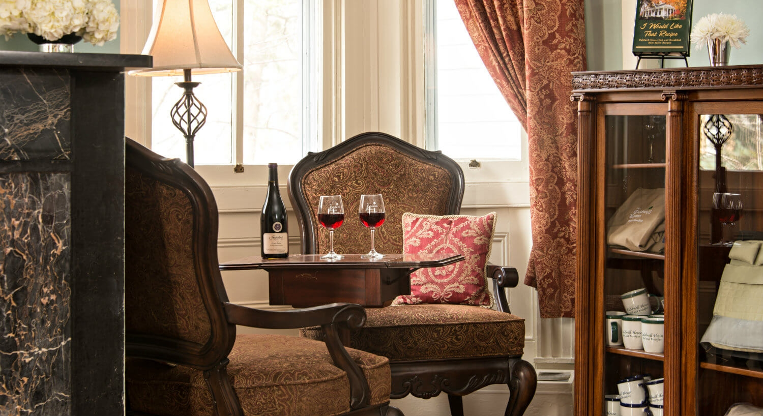 Wine is being served on a silver tray in an intimate sitting room with a cozy fireplace and seating in corner