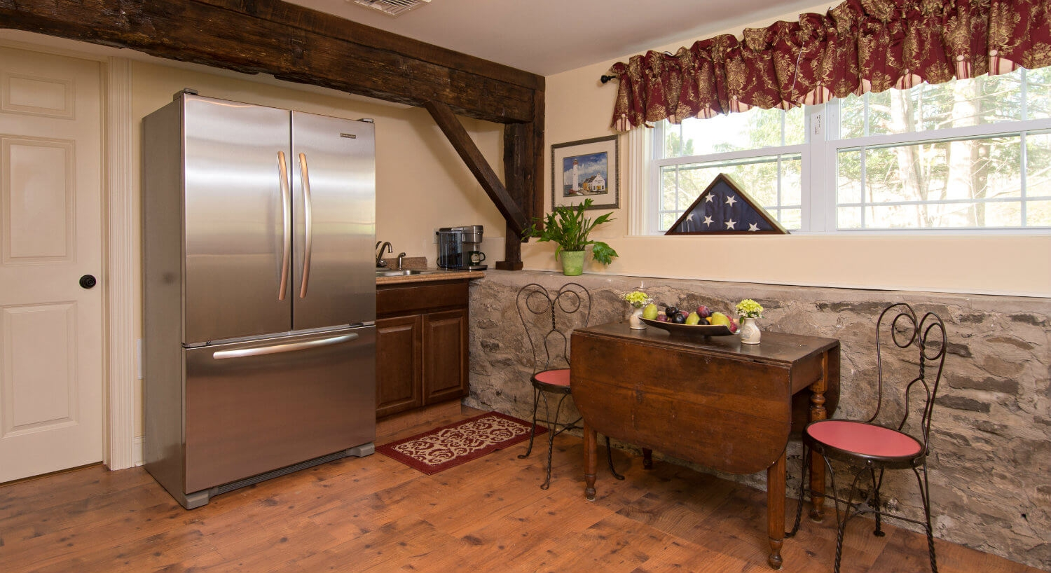 Cozy rustic kitchen with real stone wall includes a large stainless steel french door refrigerator