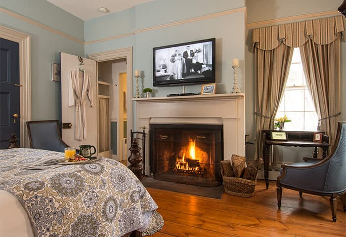 Guestroom features a neatly made bed in front of fireplace and television; walls are a soft blue with hardwood flooring
