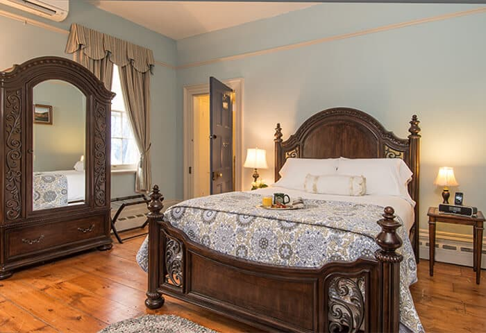Guestroom features luxurious bedding against dark wood bedframe; walls are a soft blue with hardwood flooring