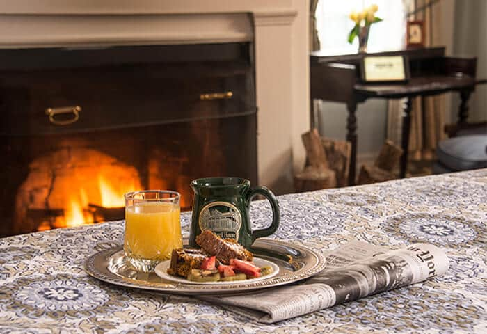 A silver tray holds coffee, orange juice, and fruit on a neatly made bed; a roaring fire is in background