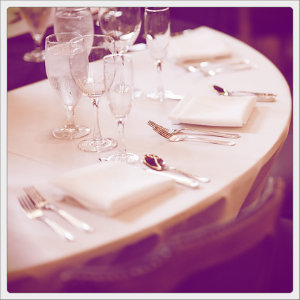 Fine dining table with white linens, white napkins, white dishes and wine glasses