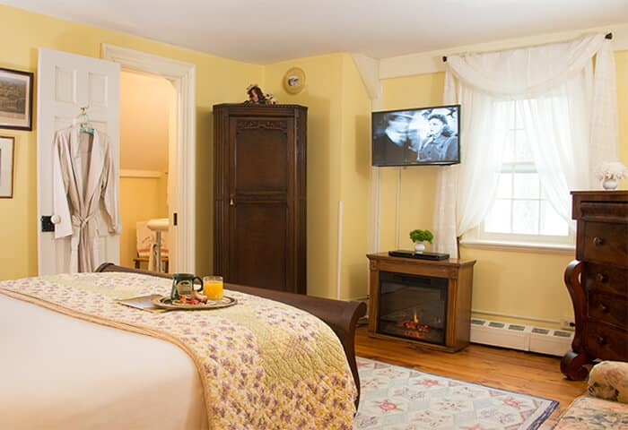 Inviting guestroom has butter-yellow walls with hardwood floors. Dark wood sleigh bed sits in front of fireplace
