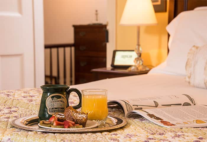 A silver tray holds coffee, orange juice, and fruit displayed on a neatly made bed