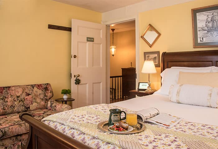 Inviting guestroom has butter-yellow walls with hardwood floors. Dark wood sleigh bed sits next to love seat