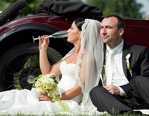 Wedding couple leaning against a luxurious burgundy coupe. They are dressed for their wedding day and sipping champagne