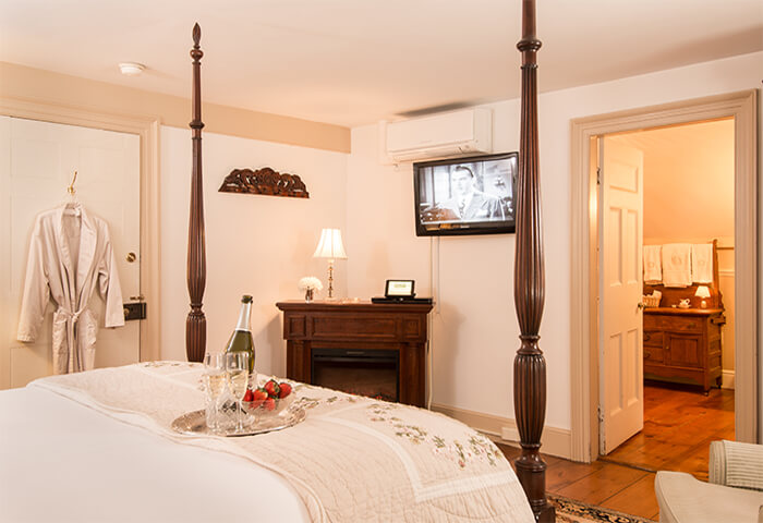 Guestroom features four post bed with a view of television and a corner fireplace