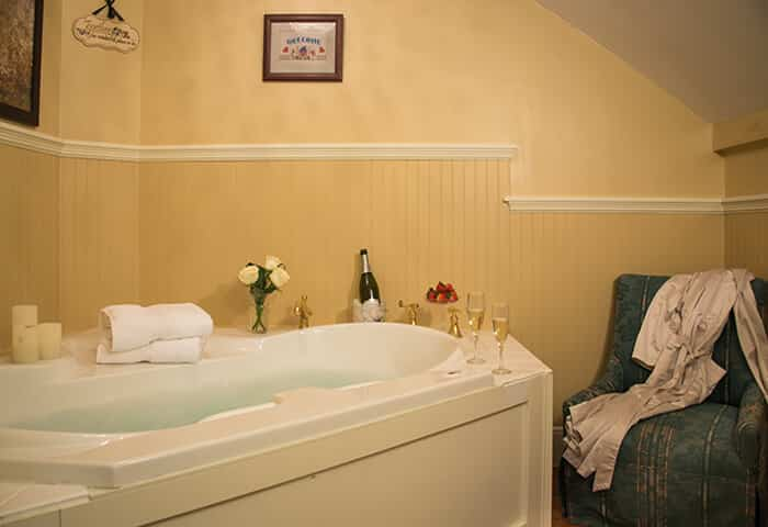 Bathroom features luxurious white tub with cream colored walls; small chair is to the side with spa amenities at hand