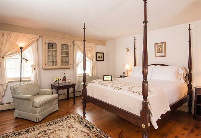 Charming bedroom with cream walls features inviting four post bed with white linens and quilt; comfy chair to the side