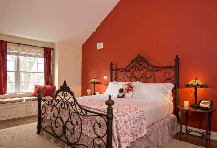 Cream colored bedroom with a red feature wall; featuring white linen bedding with floral quilt