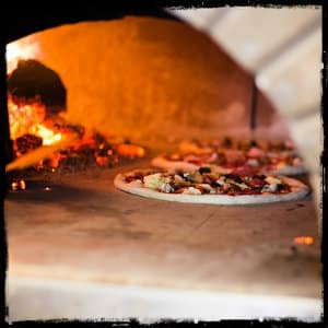 Three pizzas inside a very hot brick oven with a bright yellow and orange fire