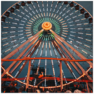 Large, colorful ferris wheel light up at night with a crowd of people below