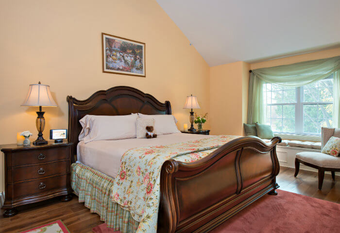 Bedroom with yellow walls has dark wooden furniture and bright white bedding with a floral quilt
