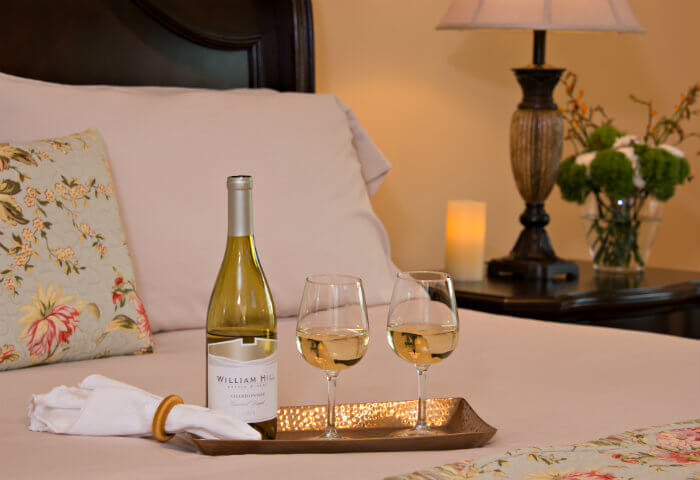 A neatly made queen bed with bright white linens features a tray with white wine and wine glasses
