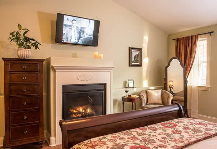 Guestroom features a roaring fireplace. Luxurious mahogany dresser sits next to wall-mounted television