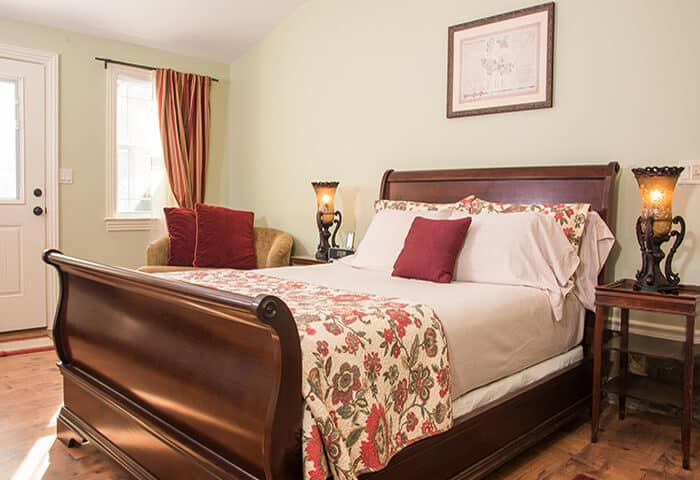 Guestroom displays soft green wall colors with hardwood floors and mahogany sleighbed; bedding is florals with cream