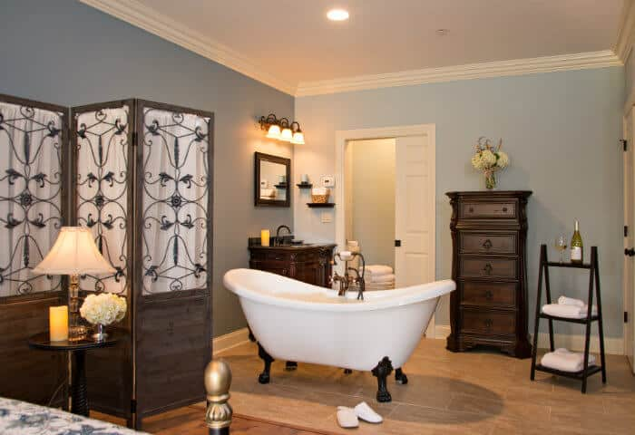 Sage blue bathroom featuring antique white clawfoot tub and dark wooden furniture