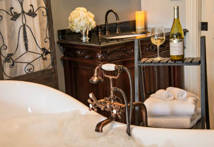 Sage blue bathroom with dark wooden vanity and white antique bathtub with towel stand featuring delicious wine