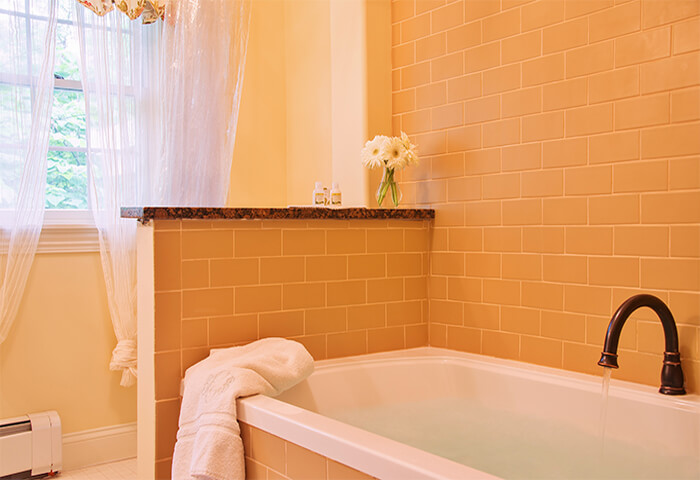 Pristinely clean bathroom features luxurious tub with bright white curtains