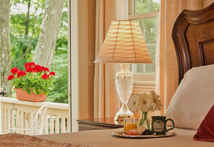 Charming guestroom displays an open door to a porch with a peek at red geraniums
