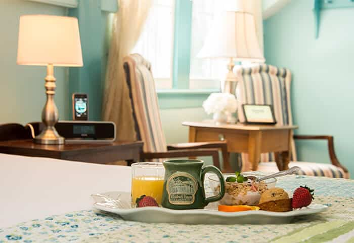 Soft blue walls in guestroom highlights tidy bed with tray of healthy snacks, coffee and juice; includes two comfy seats