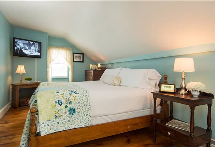 Delightful guestroom with sky blue walls featuring an antique wooden bed frame with a floral quilt draped over the bed
