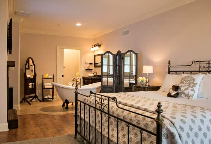 Cream walled en-suite featuring metal bedframe with white linens and antique white clawfoot tub