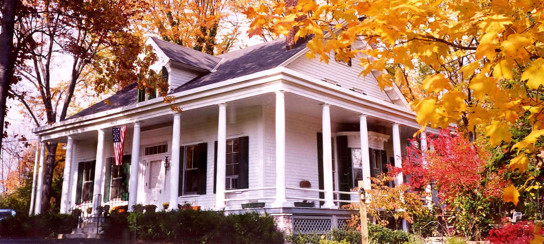 Exterior view of charming white house with numerous windows, sits among yellow and red trees of fall