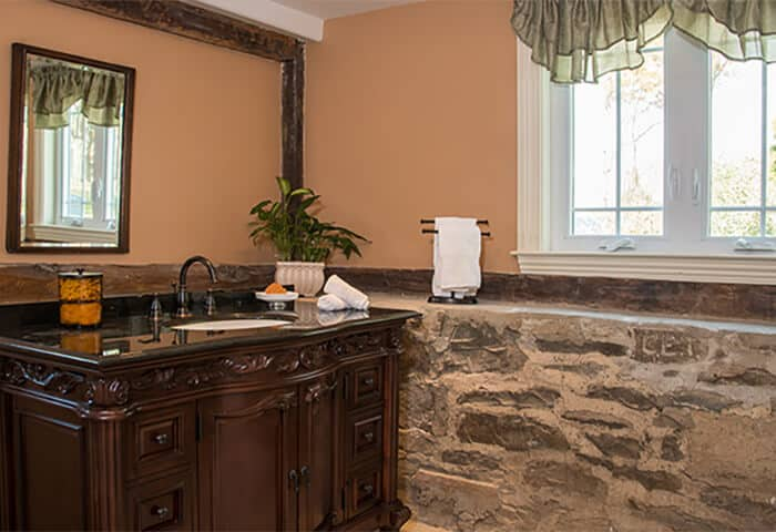 Bathroom has stonewall feature with gold wall color and dark wood vanity with mirror