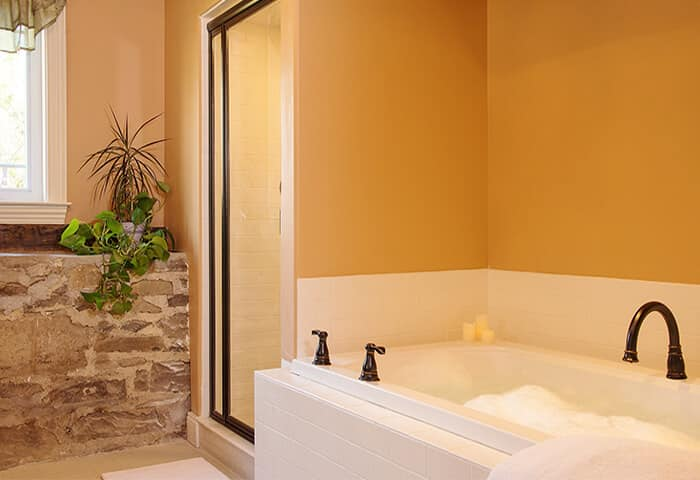 Bathroom has stonewall feature with gold wall color and white bathtub; displays spa amenities