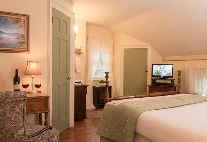 Charming bedroom with cream walls and green trim, features neatly-made bed with quilt; tv and comfy chair to the side