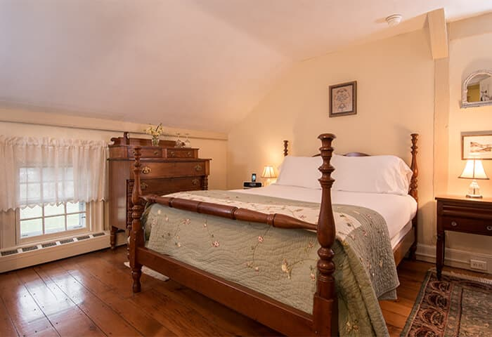 Charming bedroom with cream walls and wood flooring, features neatly made bed with quilt; also a cozy soft rug underfoot