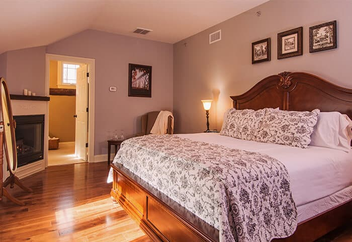 Inviting guestroom features corner fireplace and hardwood floors and neatly made bed. Wall color is a pleasing velvety heather