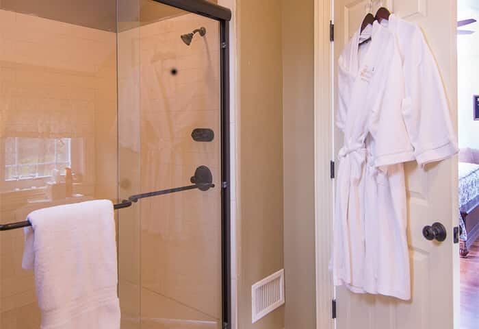 Shower in bathroom displays bright white towels, bathrobes and spa amenities