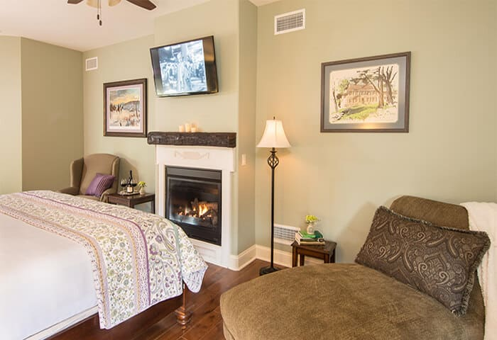 Inviting guestroom features a warm fireplace with two charming sitting areas; walls are in soft moss green, floors are hardwood