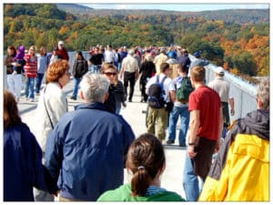 A large crowd of people walking over a long bridge with beautiful fall landscape in the background