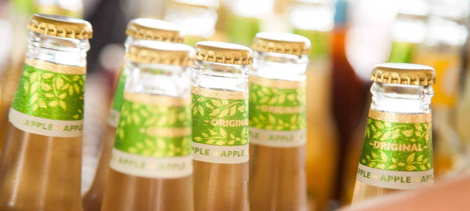 A grouping of several bottles of light apple cider with shiny green lables