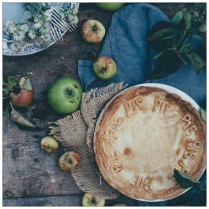 A blue denim and burlap blanket with an apple pie, plate and apples - image by annie spratt unsplash.com