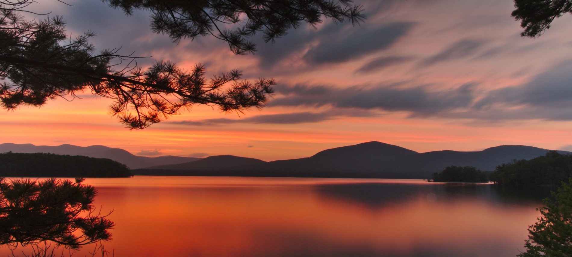 Large reservoir with view of mountain range in background surrounded by bright orange skies at dusk