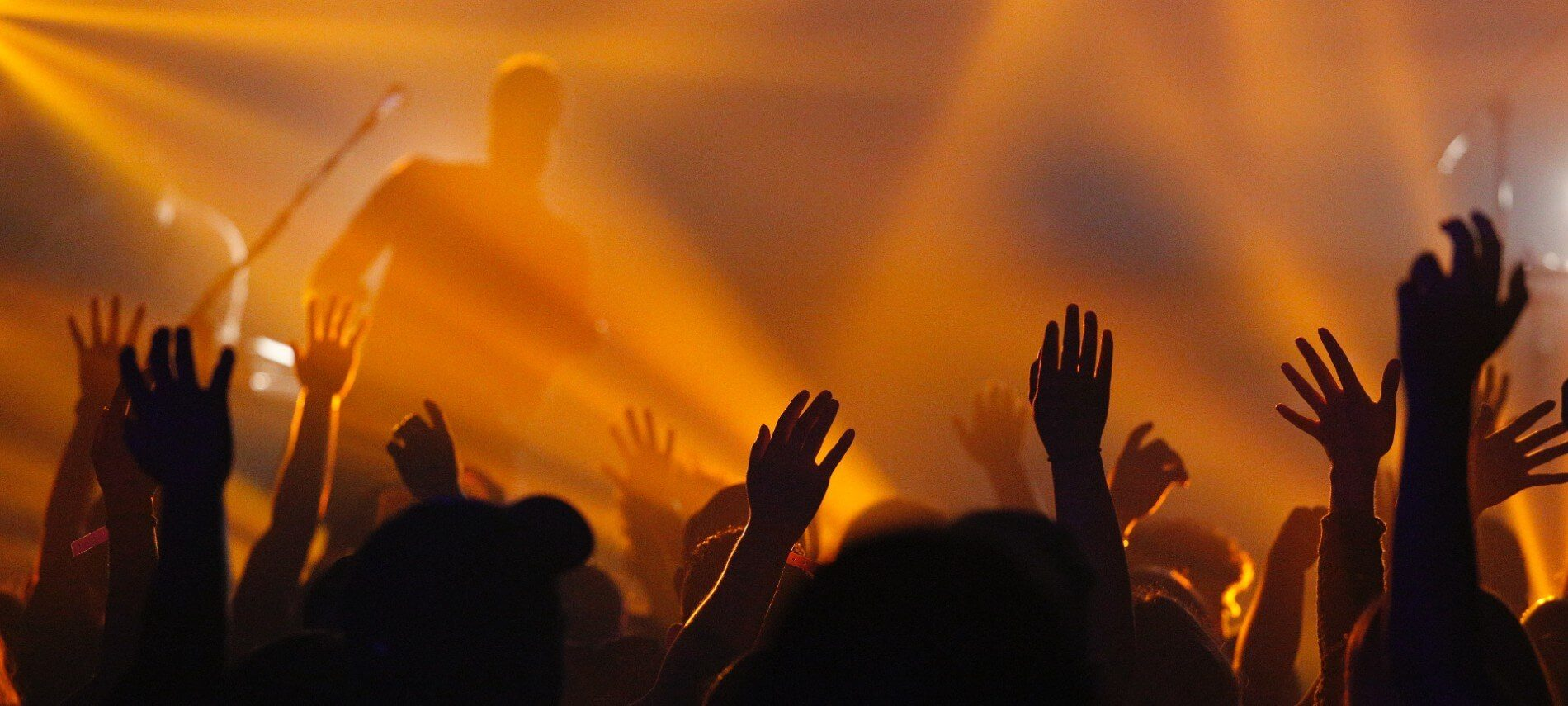 A crowd of people with hands raised in front of a stage with orange lightings and fog