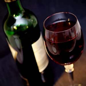 Full glass of red wine next to a dark green bottle of red wine with a cream label