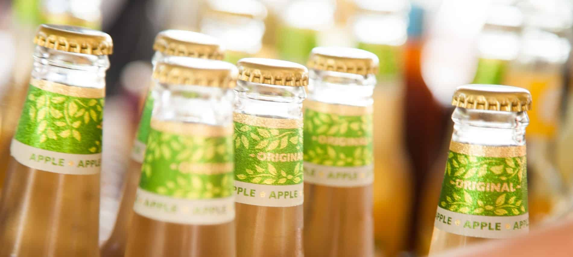 "Six bottles with gold caps and light brown beverage with green ""apple"" labels"