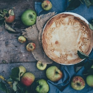 Golden brown pie on a brown burlap napkin surrounded by red and green apples