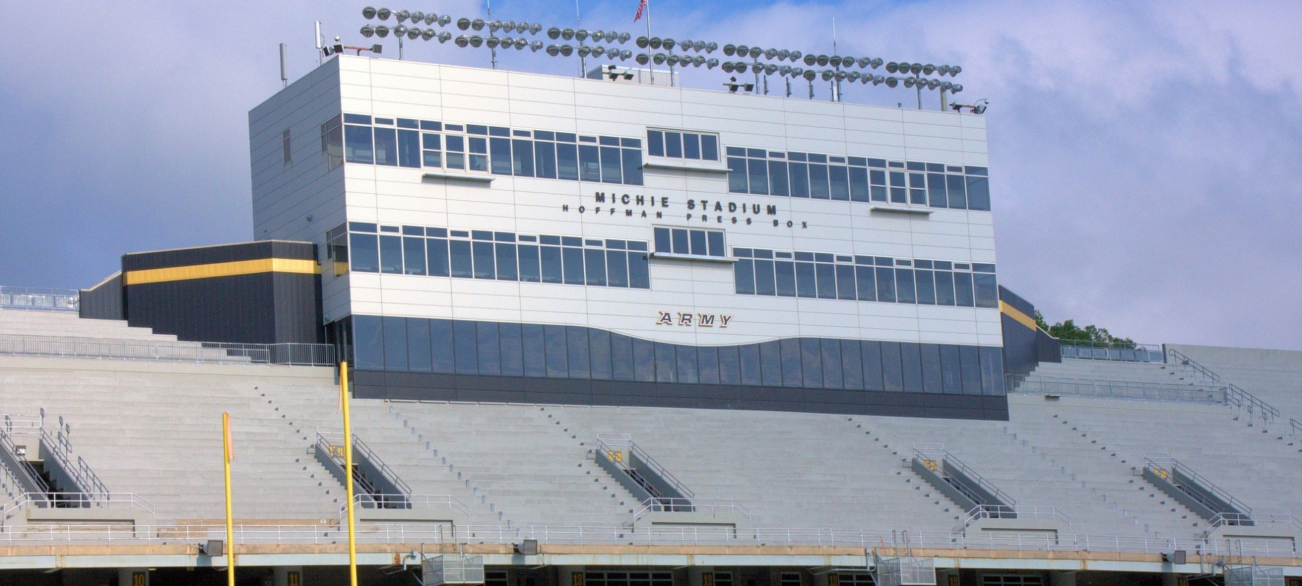 Expansive view of the outside of a large football stadium with blue sky in background