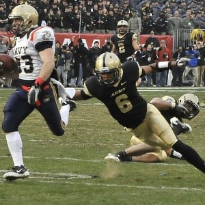 Two football players in mid play as one tries to tackle the other and full stadium crowd watching