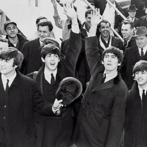 Black and white snapshot of the four members of the Beatles band standing in front of a crowd and waving